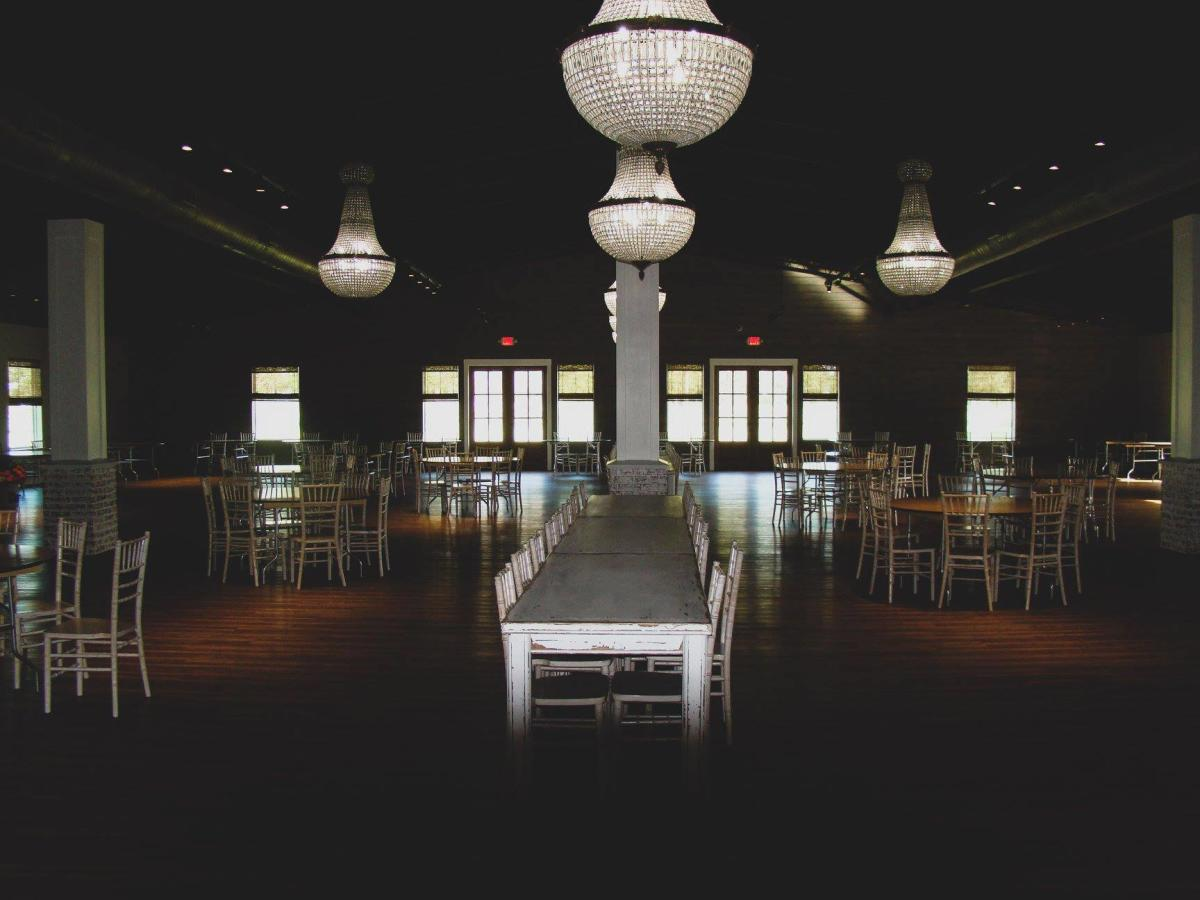 The reception space of Venue at Belle Oaks has hardwood floors and elegant chandeliers.