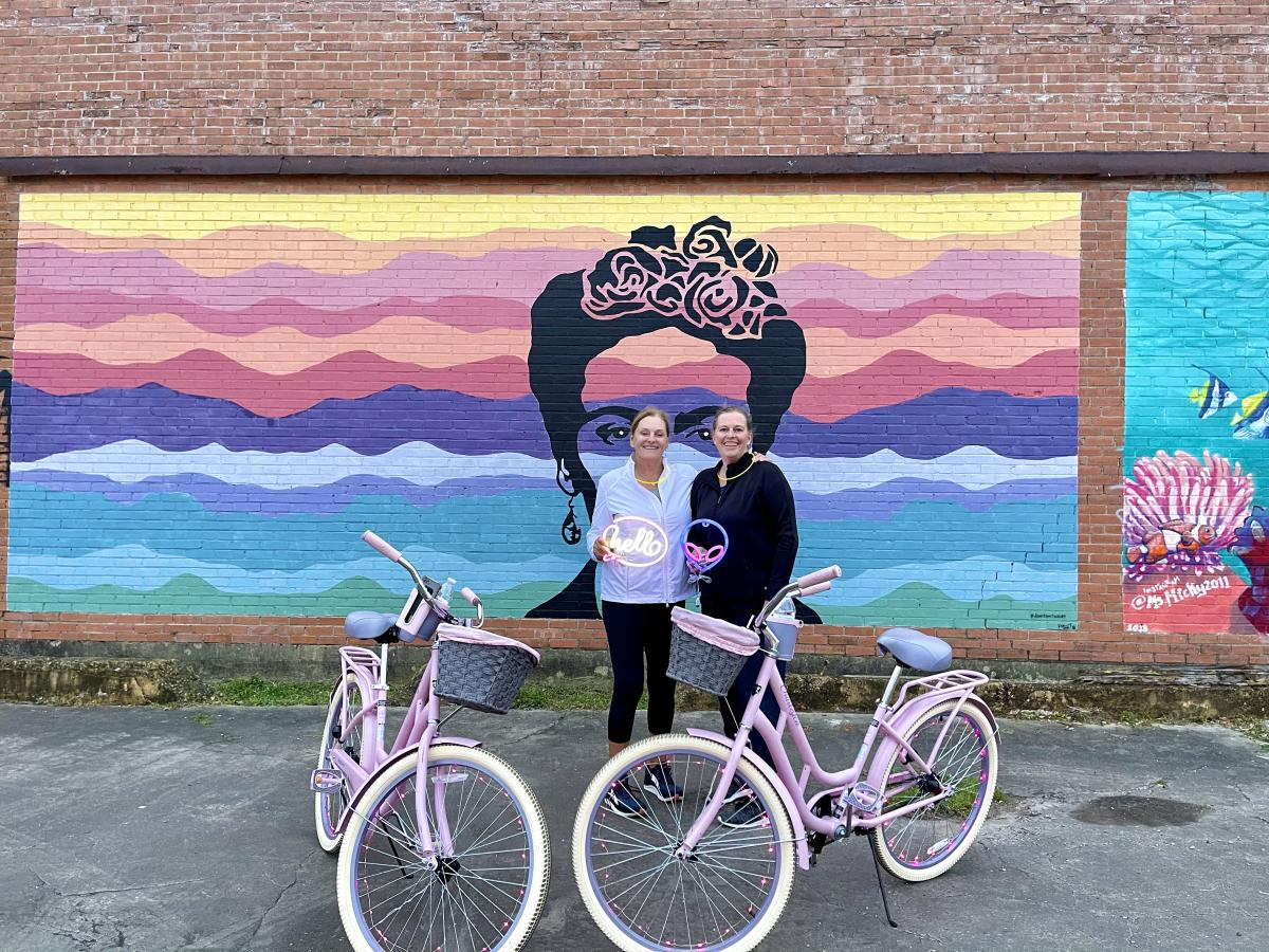 Two Woman With spindletop cruisers bikes In front Of A Frida Mural