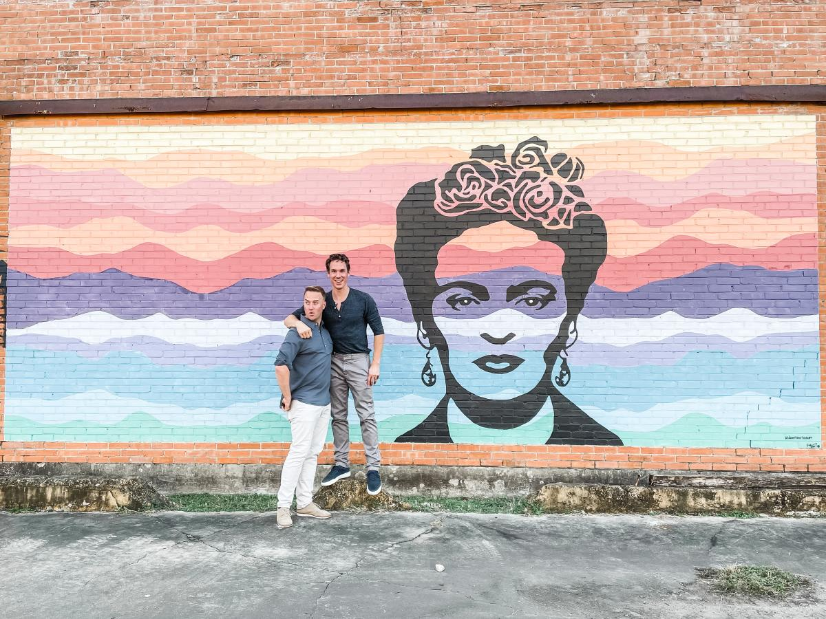 Couple posing in front of a Frida mural in Beaumont