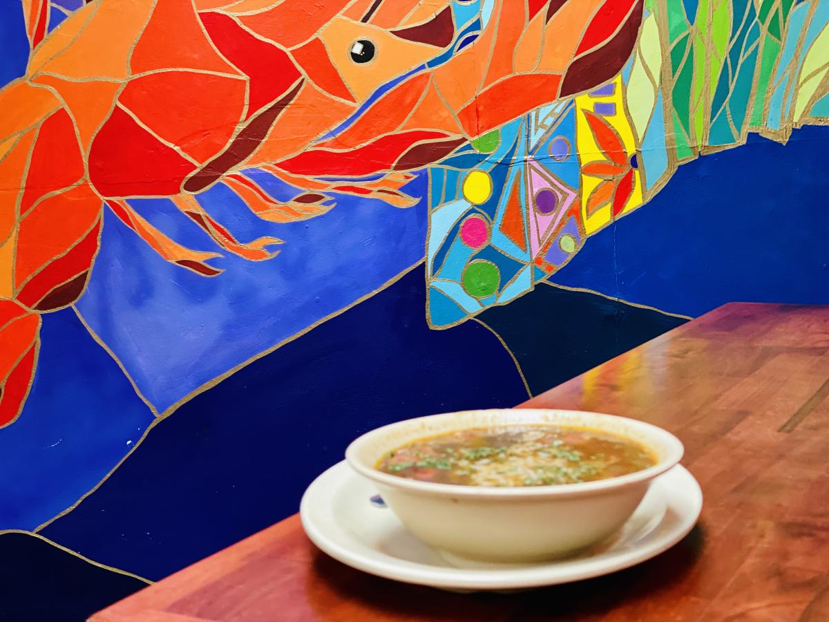Bowl of gumbo on a table with a tile mural in the background at Crazy Cajun