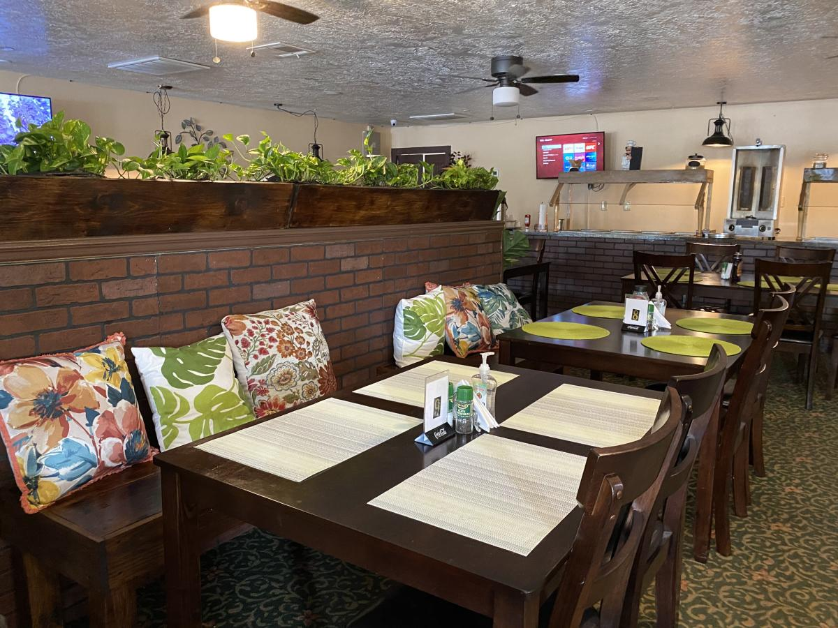 The interior at Green Leaf combines rich wood with live plants and fabric cushions.