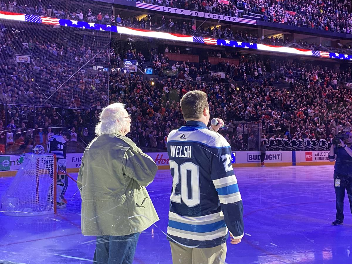 Military Veteran, John Weimer stands on the ice at Nationwide Arena for the singing of the National Anthem with Leo Welsh during a Columbus Blue Jackets game.