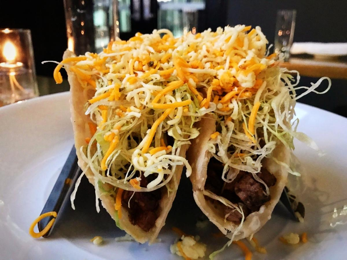 Two Cheesy Brisket Crunch tacos on plate at Service Bar, piled high with meat and cheese