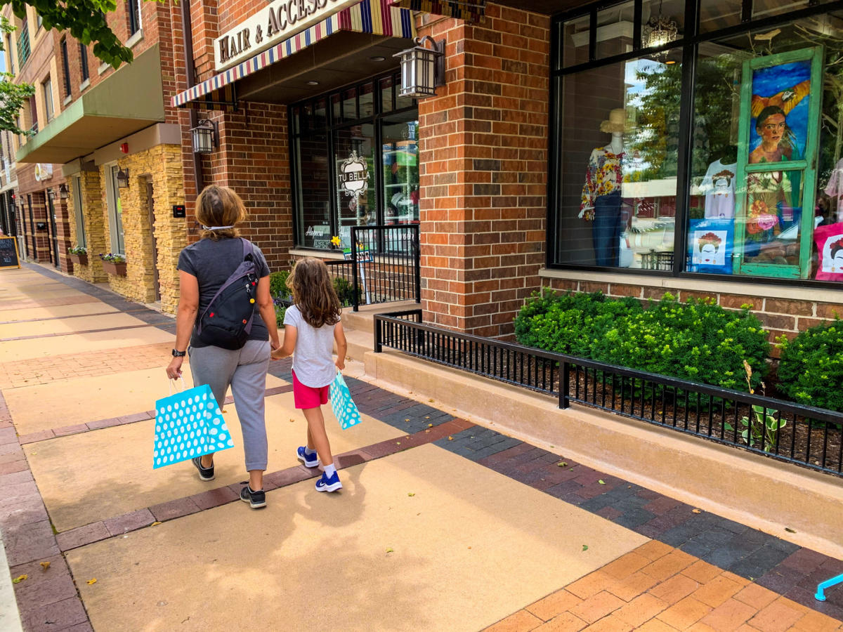 Mom holding daughters hand shopping in Downtown Lisle