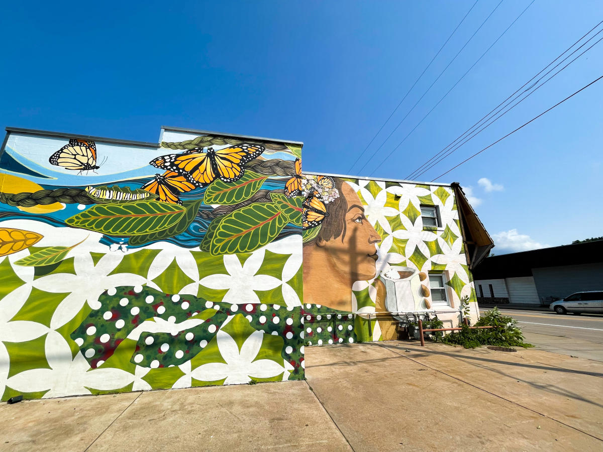 Mural located on side of building on Birch St. of a woman with butterflies flying around her head