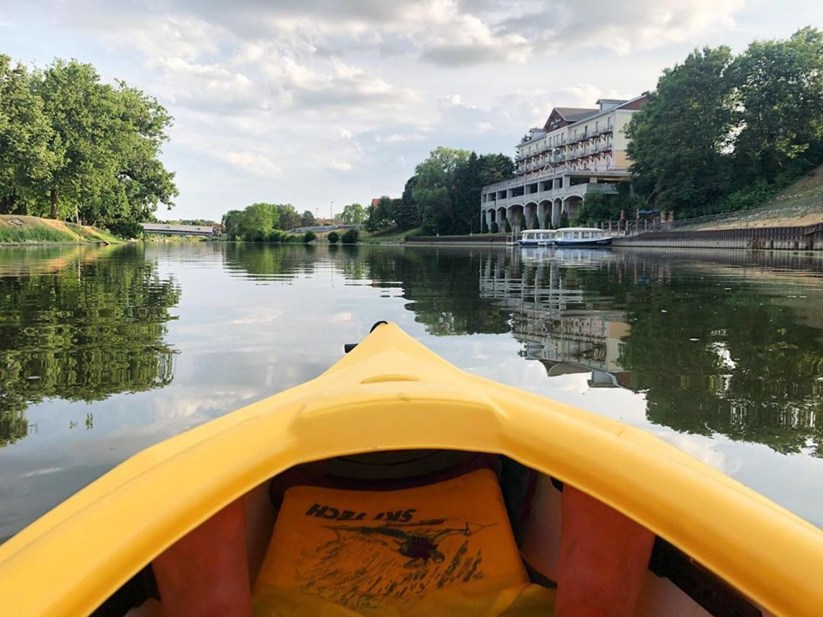 Views from a bright yellow kayak on the Cass River in Frankenmuth, with the Marv Herzog Hotel reflected on the water