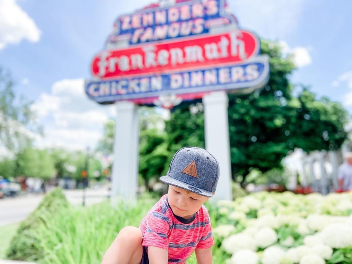 Little boy sitting in the flowers in front of the Zehnder's Famous Frankenmuth Chicken Dinners sign