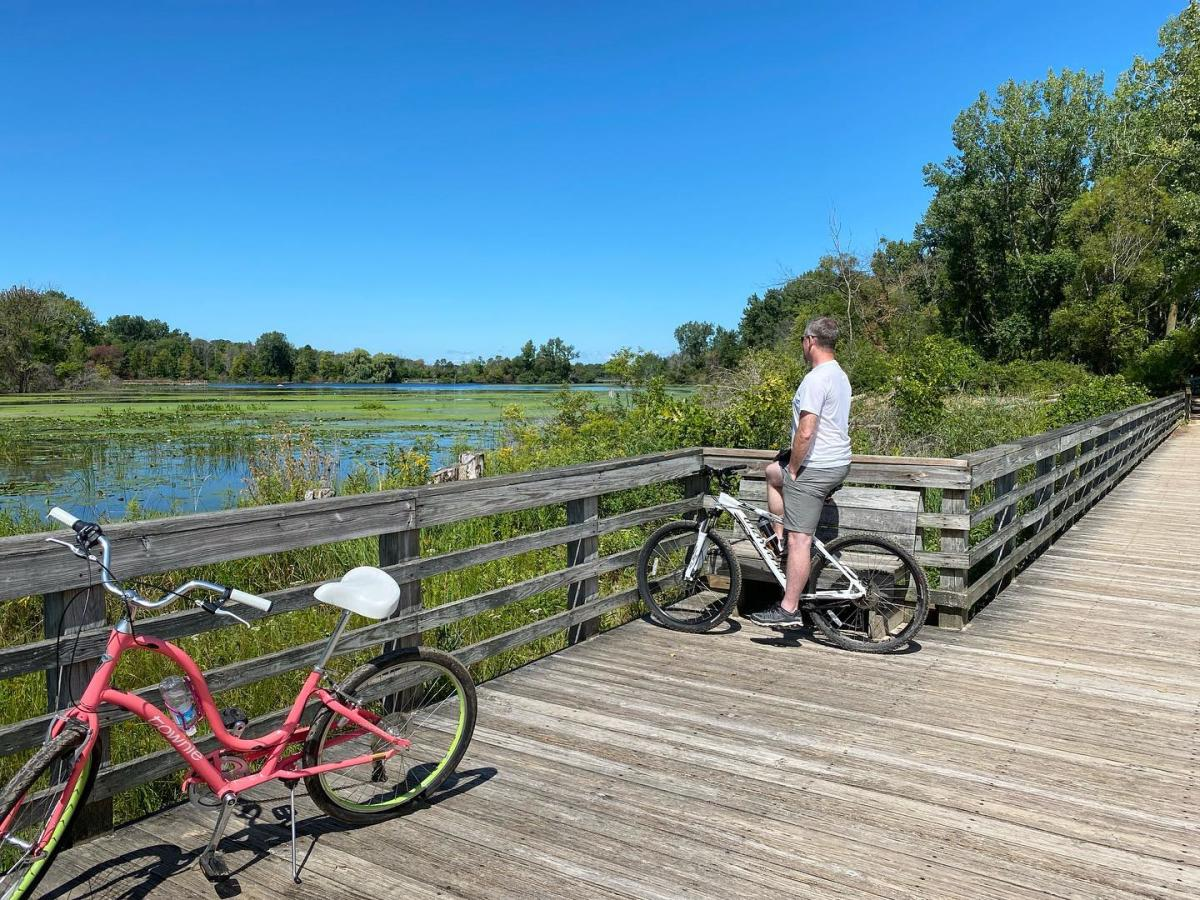 Man on a bike looking out over Tobico Marsh on a boardwalk trail at Bay City State Park