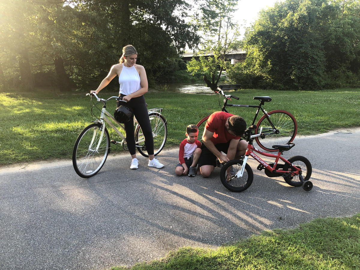 A father helps his son fix his bike while the mom looks on