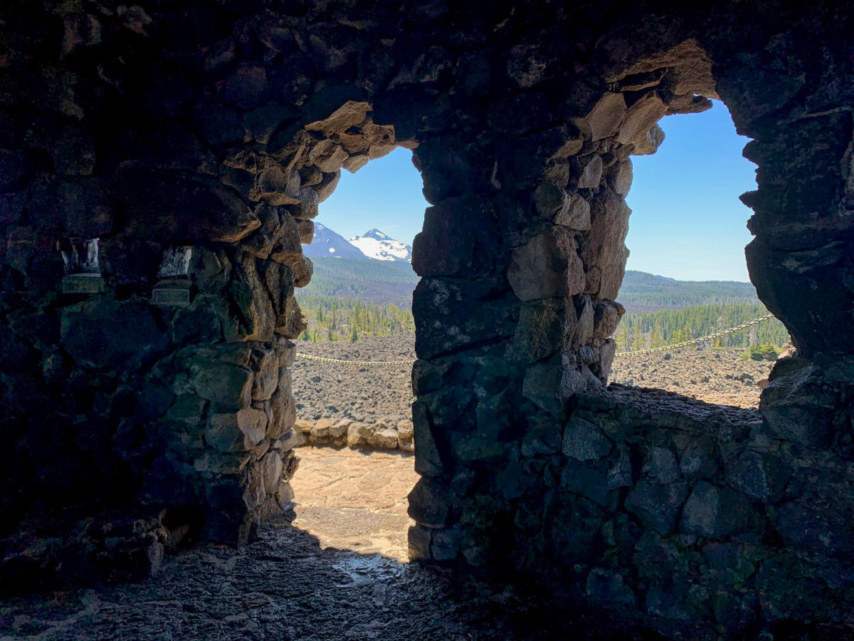 Photo is taken from inside a lava rock fort, looking out through a doorway and window showing snowy mountains in the distance.
