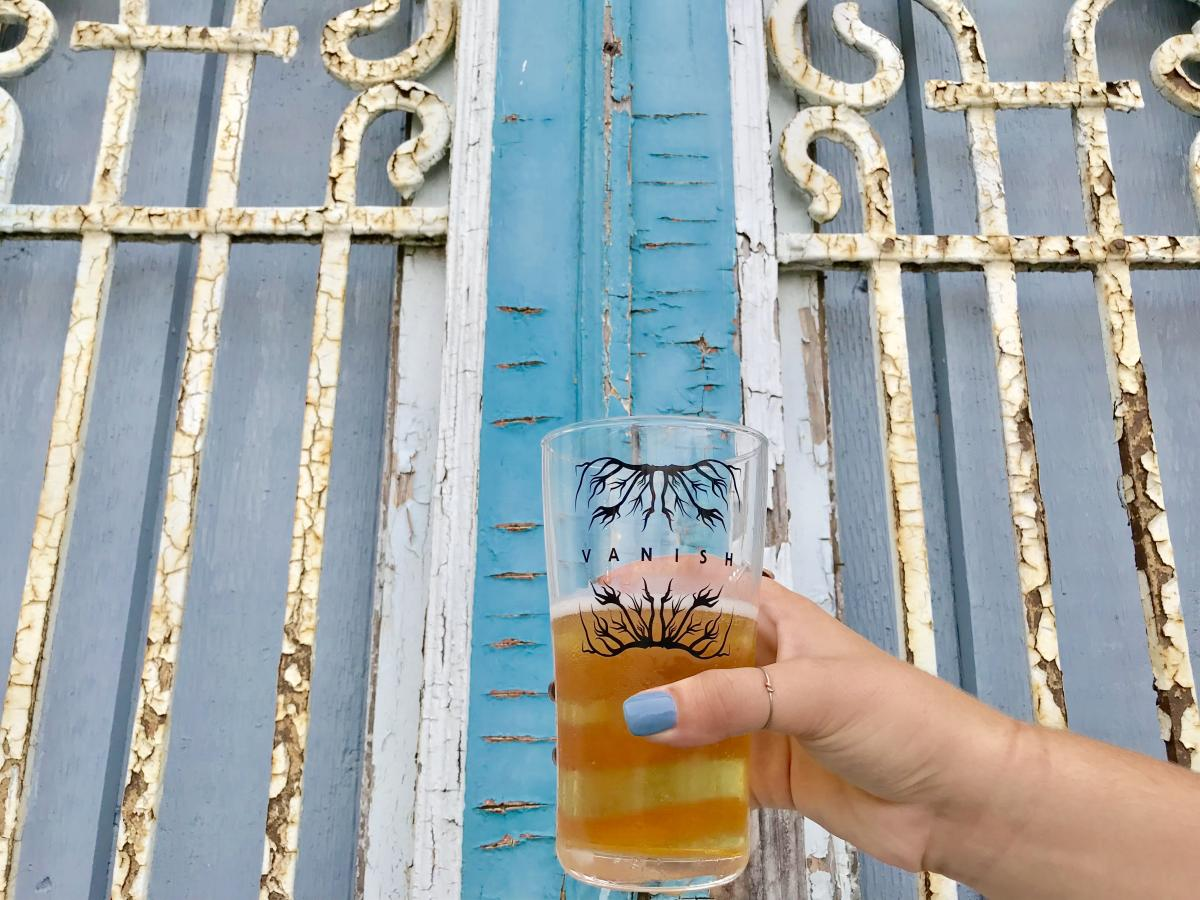 """A woman's hand holds up a glass filled with beer in front of a rustic iron gate with peeling white paint. The glass is marked """"Vanish Beer"""""""