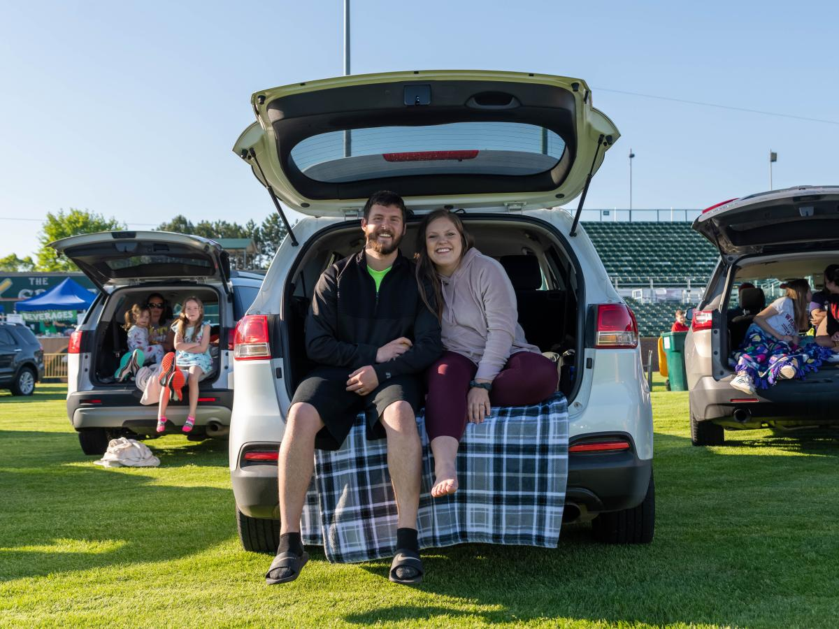 A couple sits on the trunk of their vehicle waiting for a drive-in movie to begin
