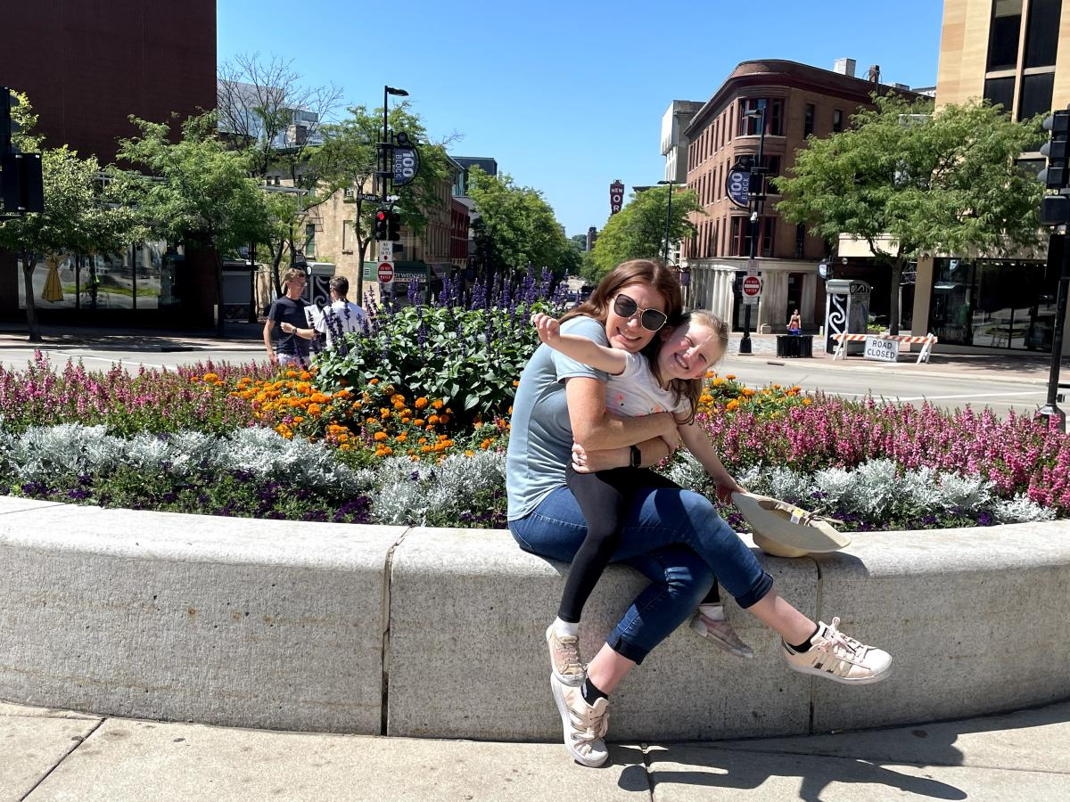 A woman and daughter pose by flowers at the Top of State Street