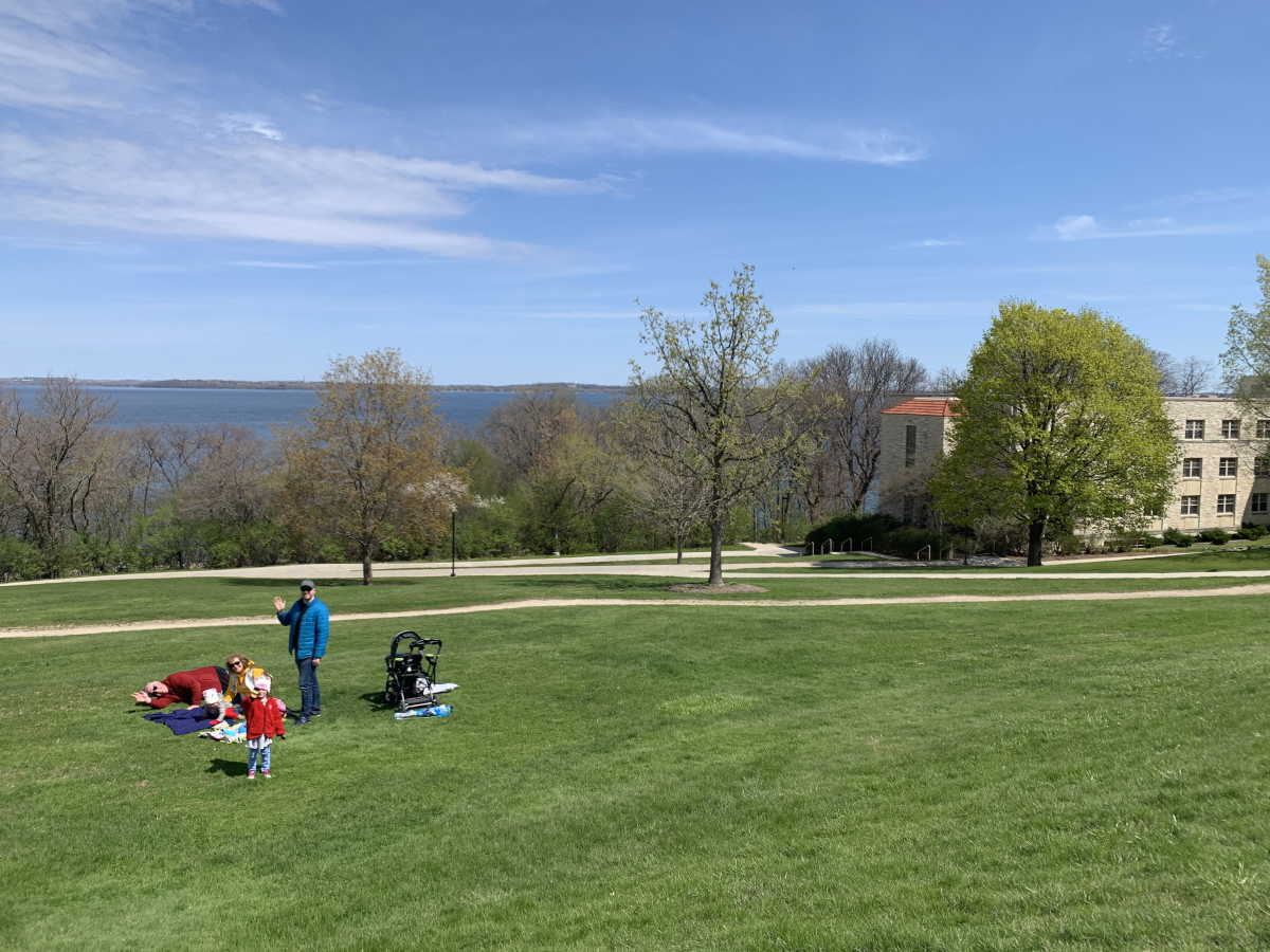 A family sets up a blanket on Observatory Hill in preparation for a picnic