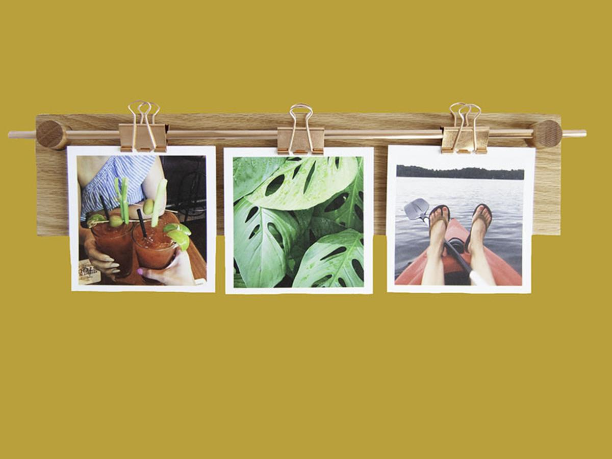 Polaroid photos hang from paper clips on a handcrafted item from Mad Makery