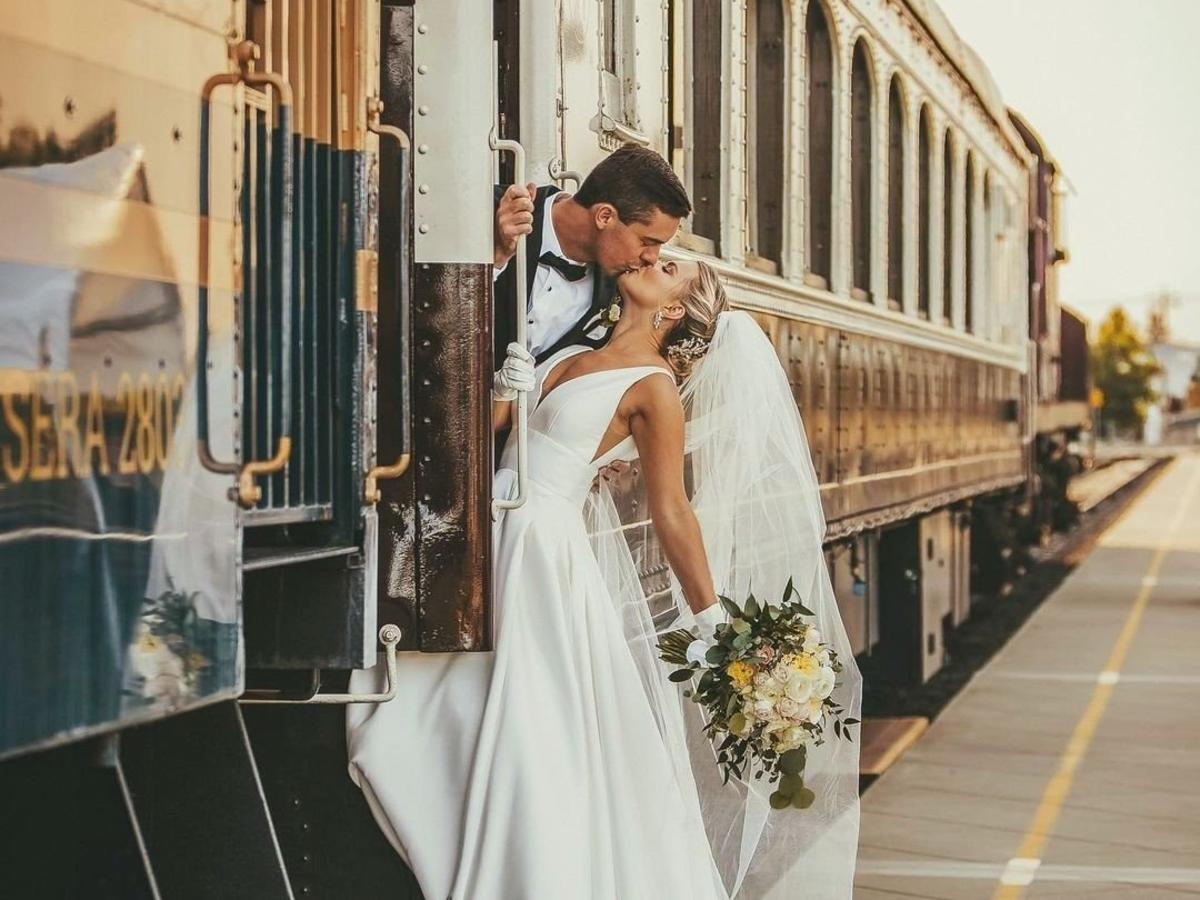 Bride and groom kissing off train for a Wine Train Wedding