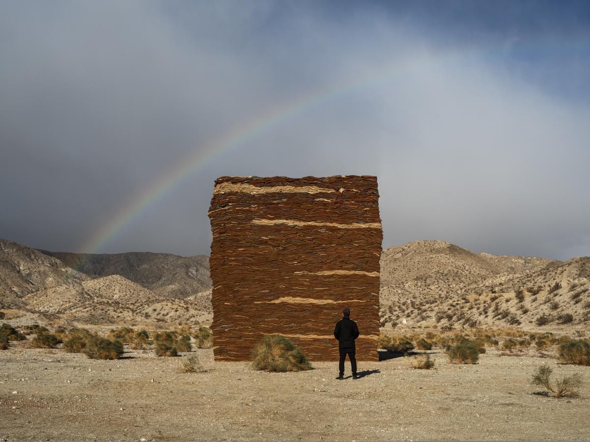 Wall of clothes art in the desert with a rainbow