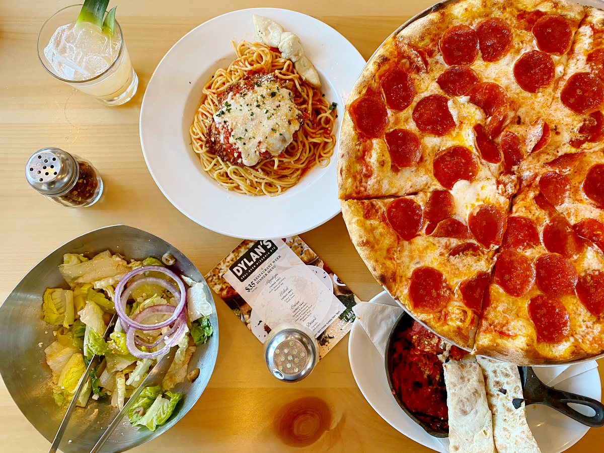 Aerial shot of pepperoni pizza, salad, pasta, spice shakers, and lemonade on wooden table