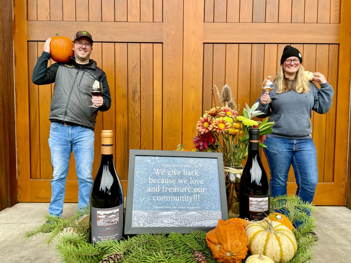 """Lemelson winemakers hold Giving Season sign reading """"we give back because we love and treasure our community"""""""