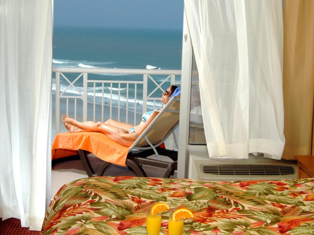 Woman sunbathing on balcony at holiday Inn Resort