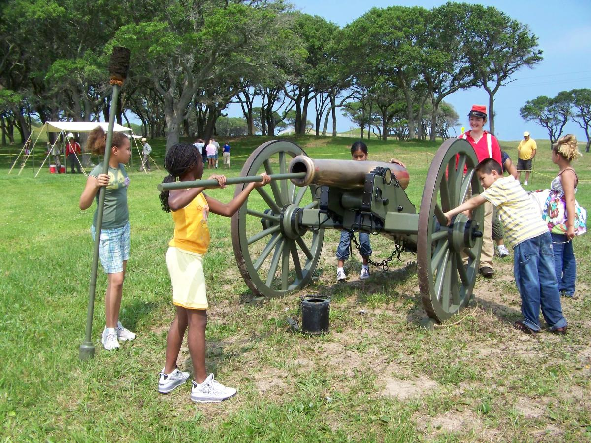 Kids pretend to load historic cannon at Fort Fisher State Historic Site