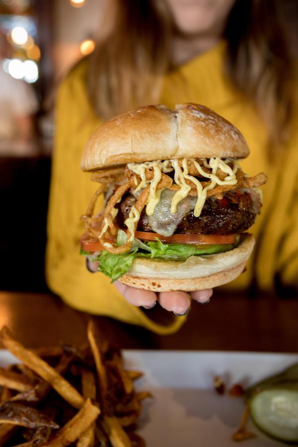 Woman hold a burger at Jo's American Bistro in Newport RI