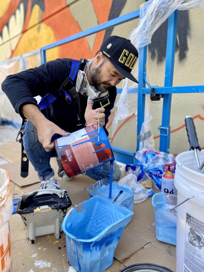 Artist pouring paint into tray in preparation of painting a large mural.
