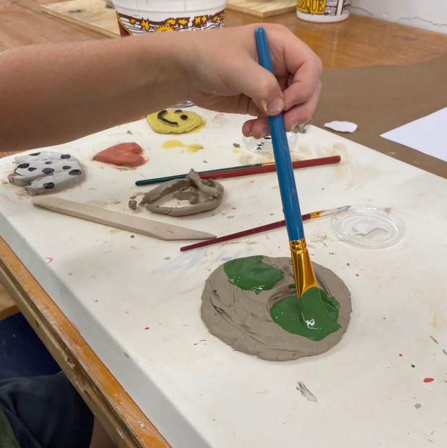 child's hand painting clay