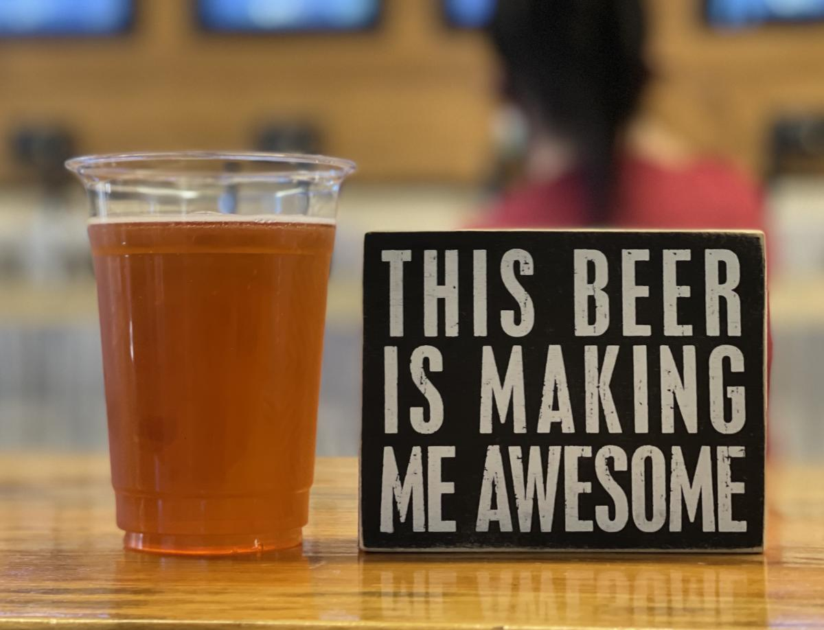 beer next to sign saying this beer is making me awesome