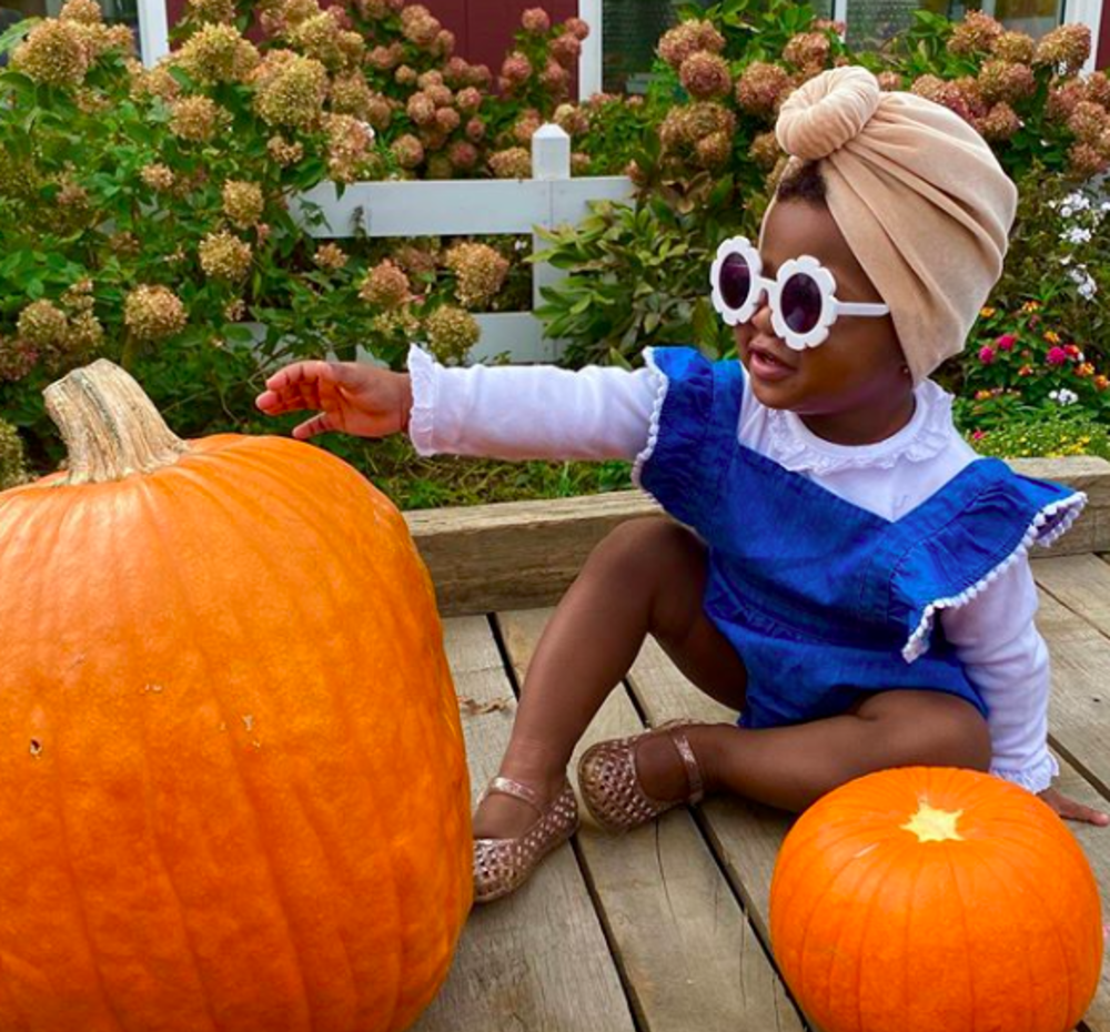 A little girl in sunglasses with a pumpkin at terhune orchards