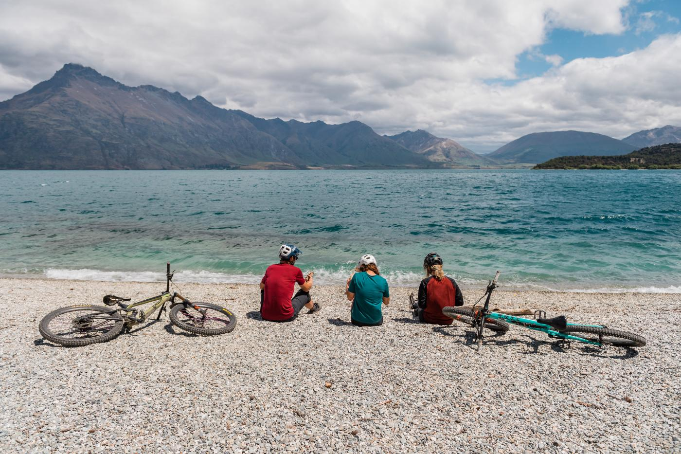 Friends sitting by the lakeside at 7 Mile Scenic Reserve, Queenstown