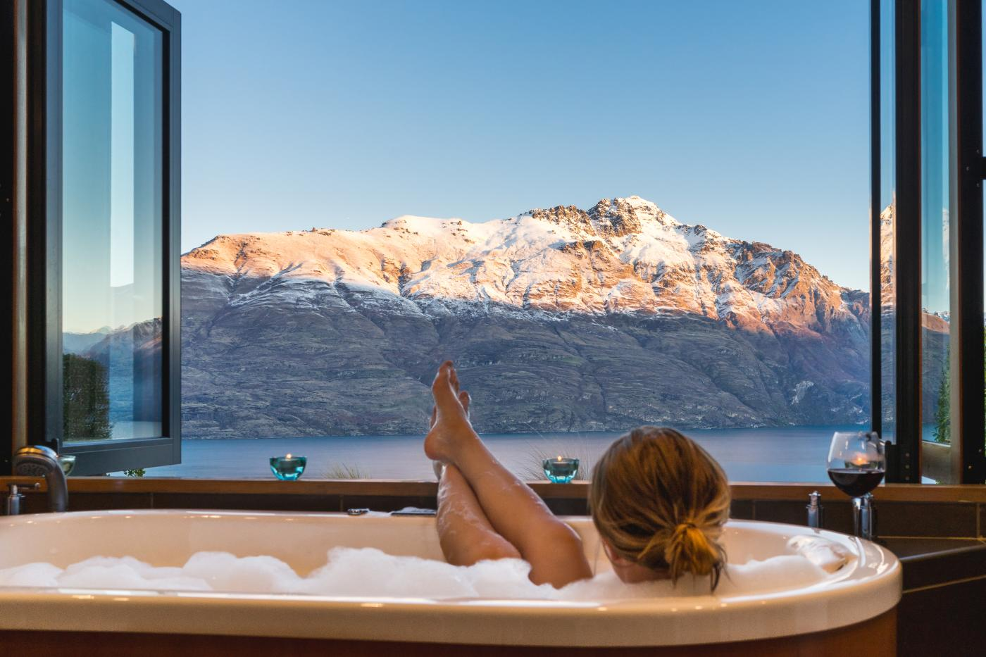 Woman relaxing in bath at Azur Lodge