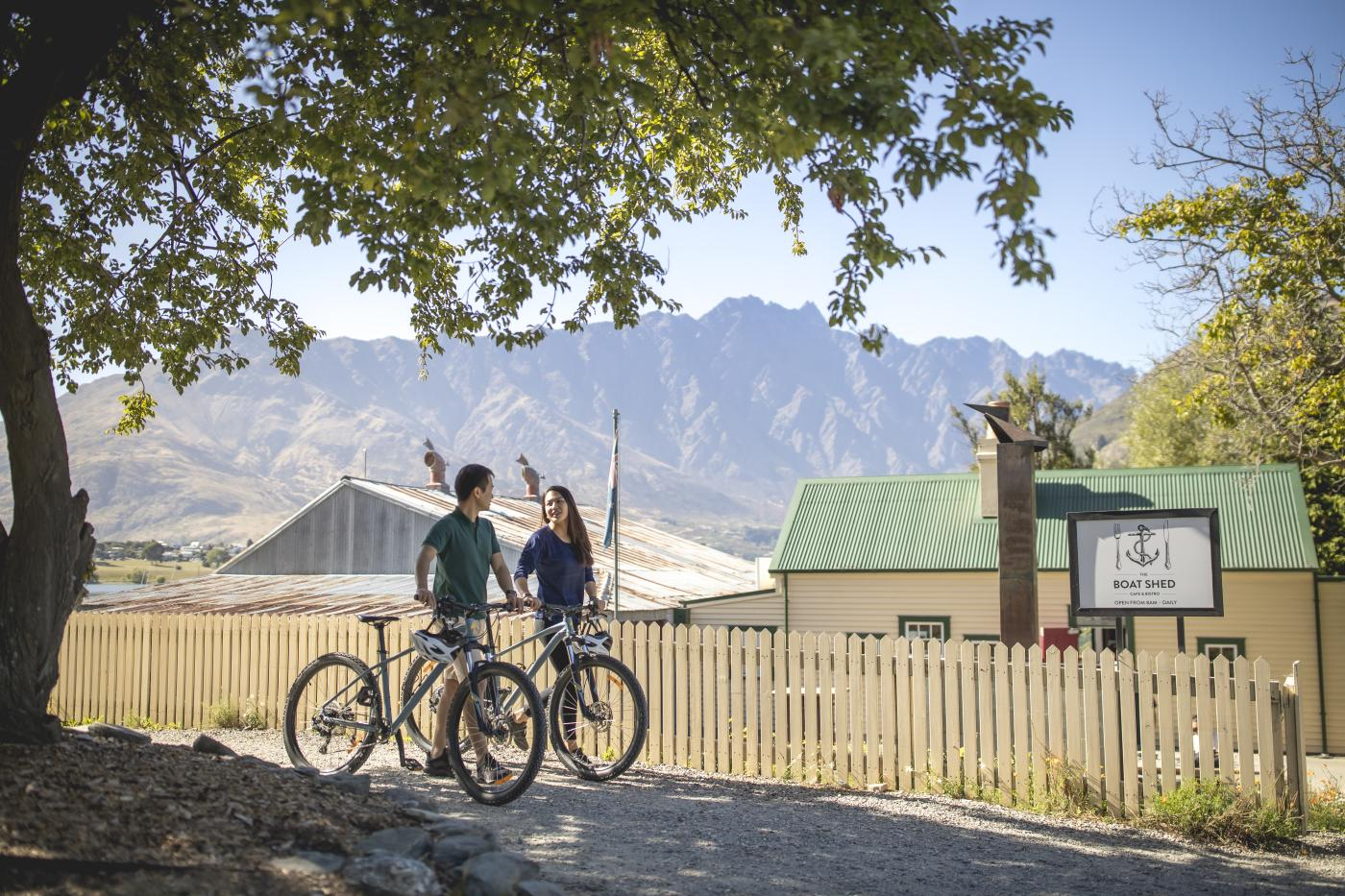 Couple biking The Queenstown Trail, by the Boat Shed Cafe