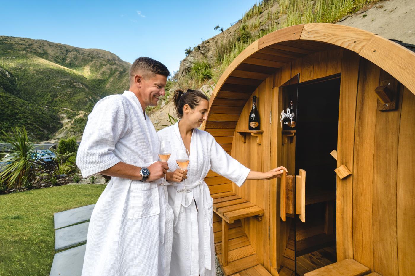 Man and woman entering a wine-barrel sauna