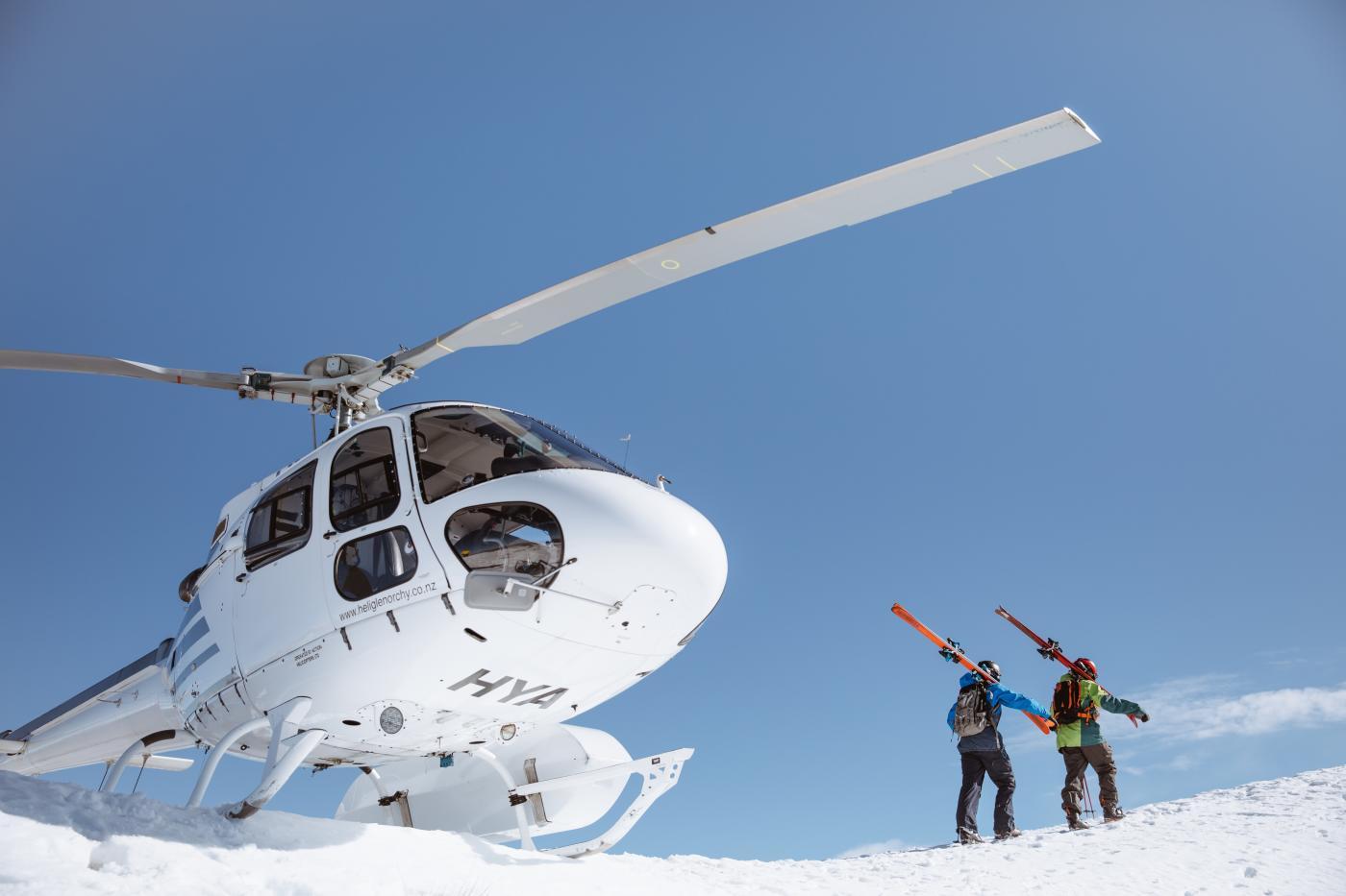 Heli Skiing landing on mountain with skiers