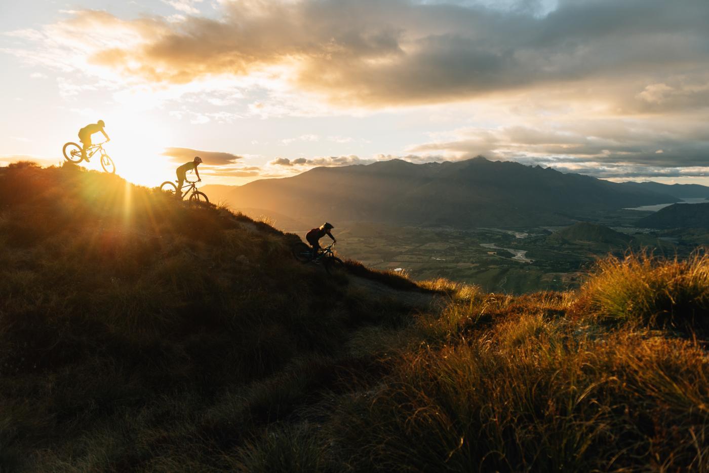 Mountain bikers at sunset biking Rude Rock, Coronet Peak Mountain Bike Trail