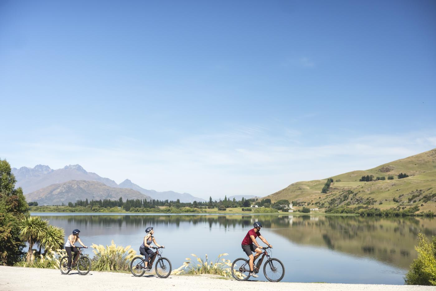 Friends biking Lake Hayes loop track in Summer