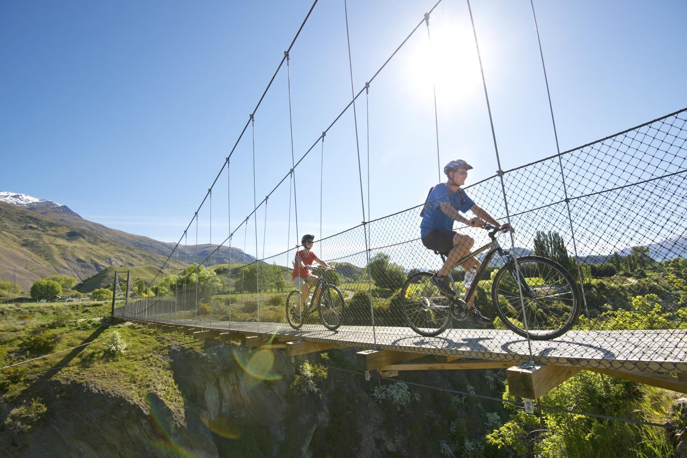 Couple Summer Biking over Edgar Bridge Gibbston