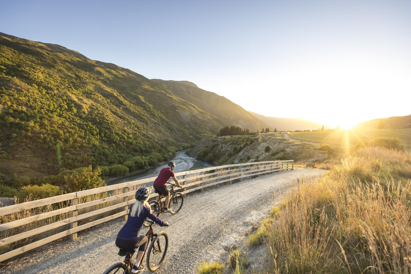 Couple cycling the Gibbston River Wine Trail