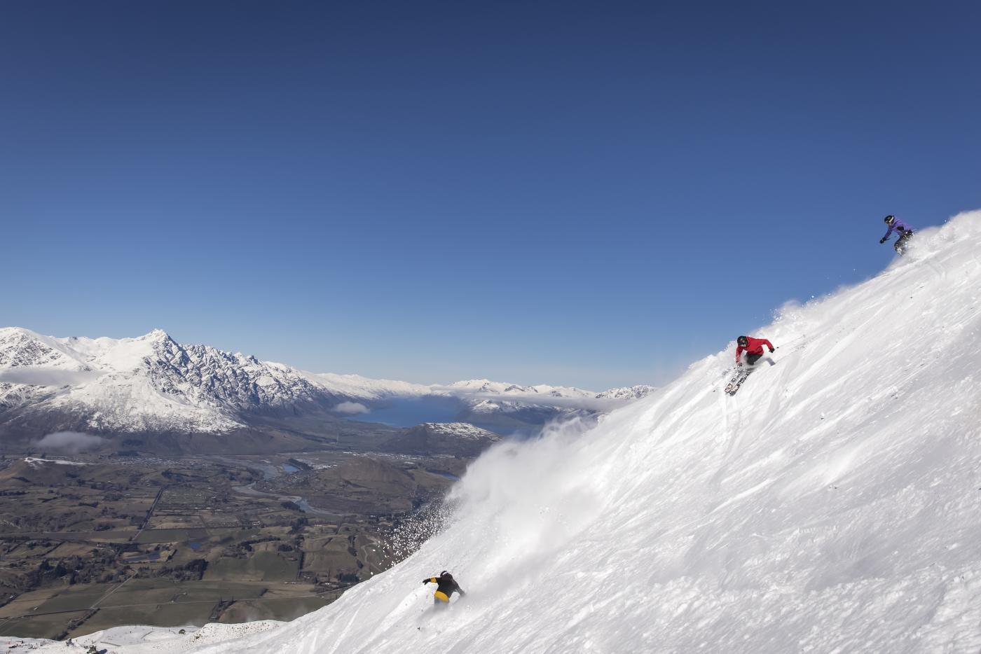 Friends skiing Coronet Peak on a bluebird day