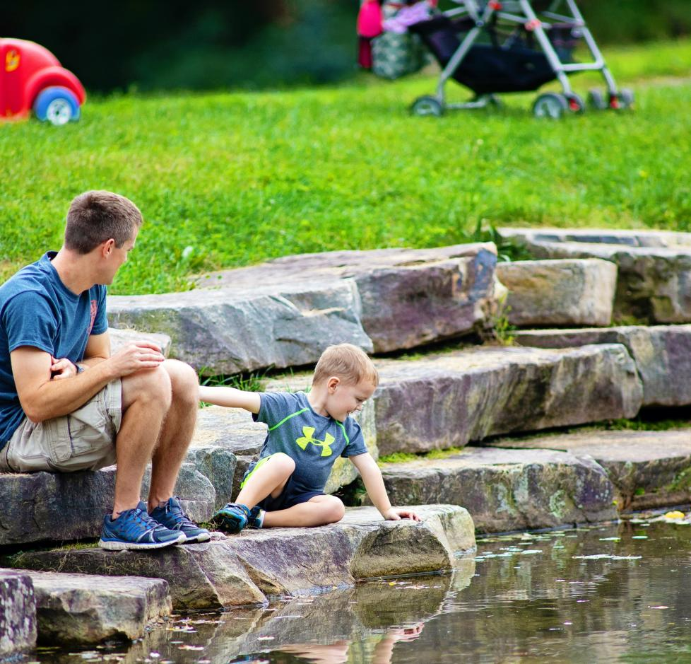 Family playing near pond at McDade Park