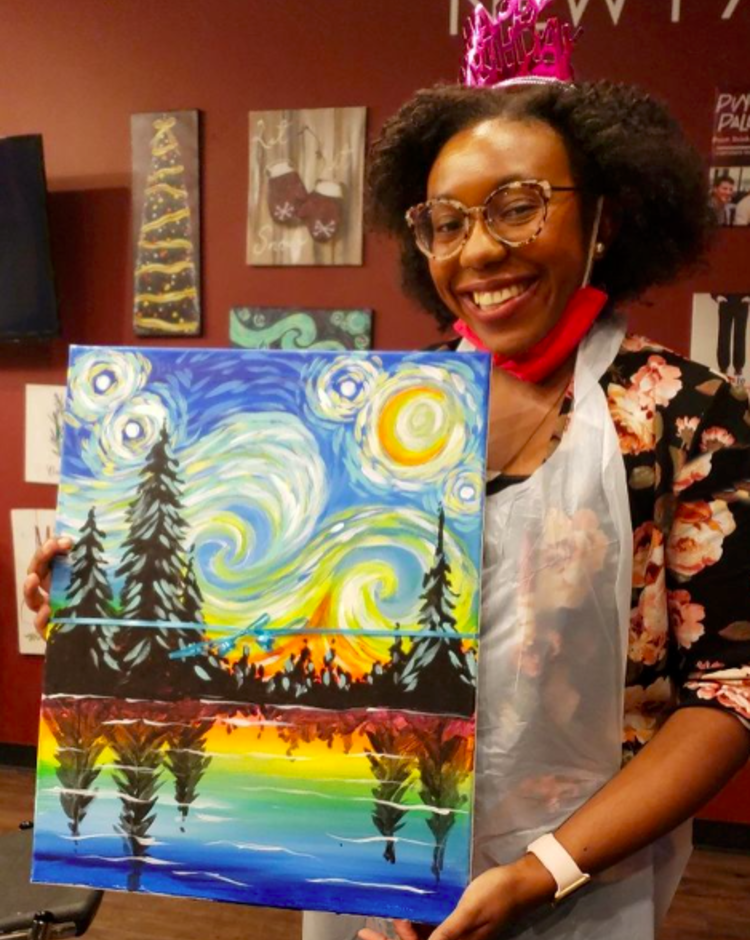 A woman holding a completed scene painted at Pinot's Palette in Princeton, NJ.