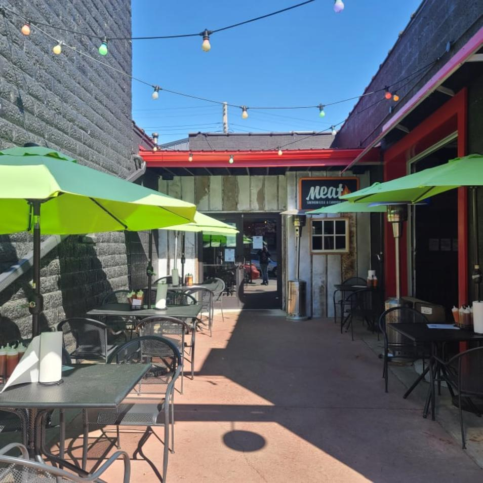 Colorful patio umbrella tables on the courtyard patio outside of MEAT Southern BBQ