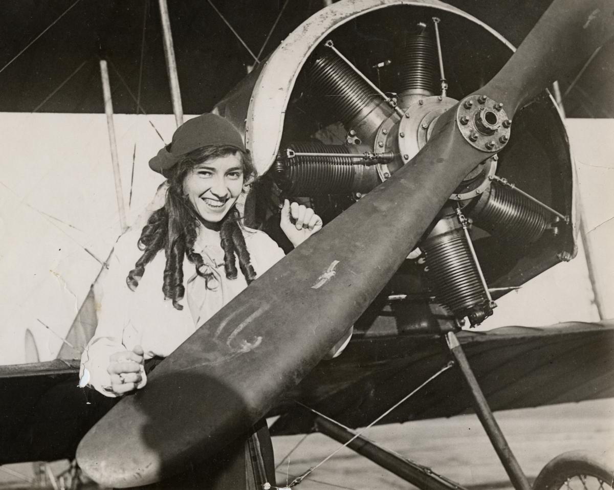 Pilot Katherine Stinson posing behind a propeller head, ca. 1910–19