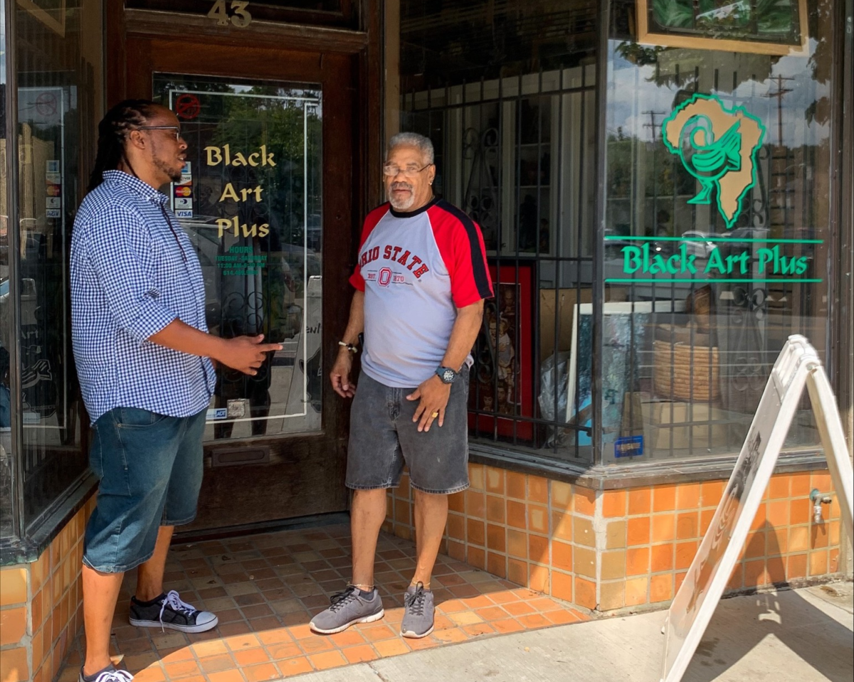 Artist Evan Williams chats with a man outside Black Art Plus