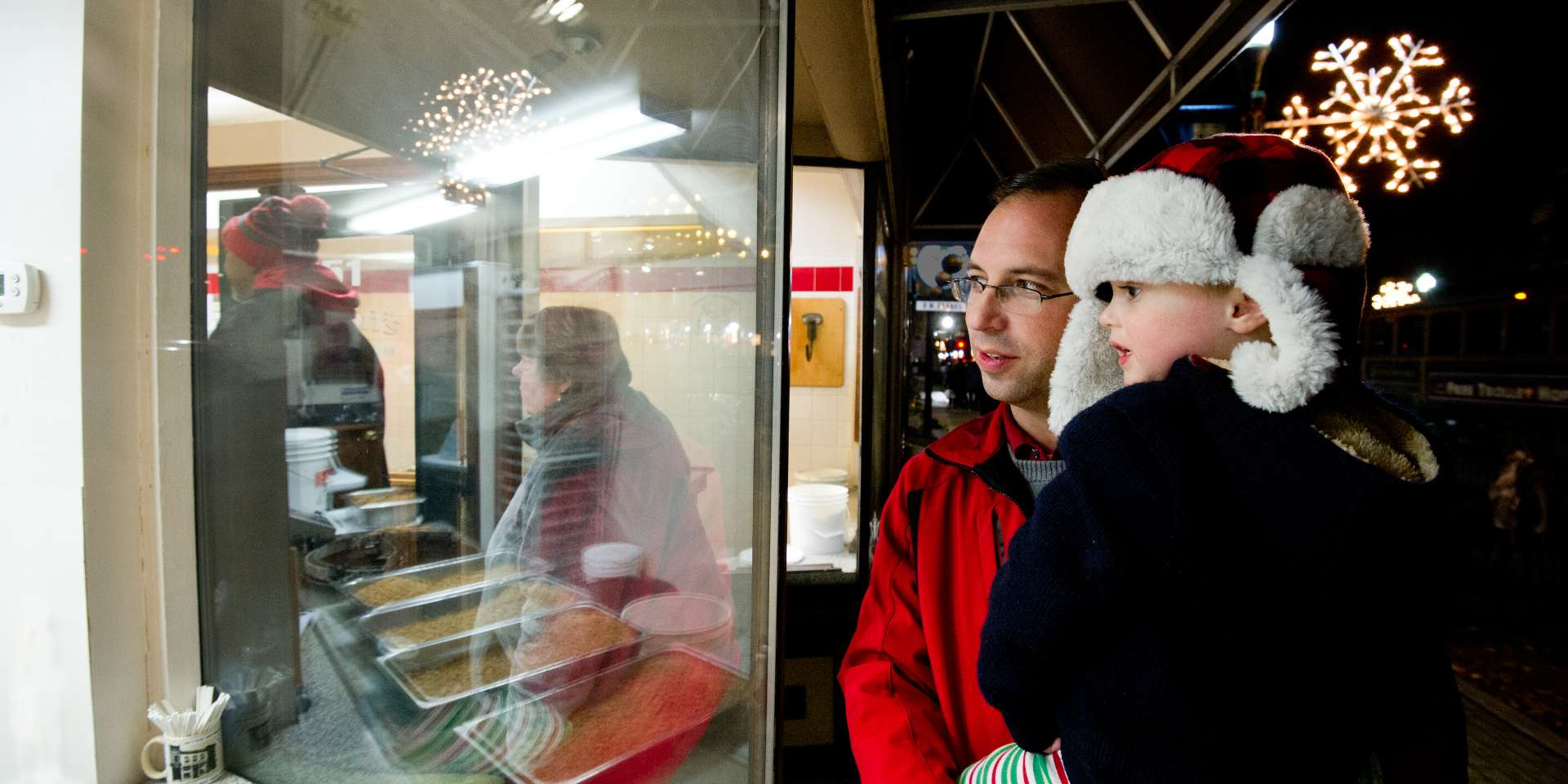 Man holding boy looking in the Schimpff's window at wintertime