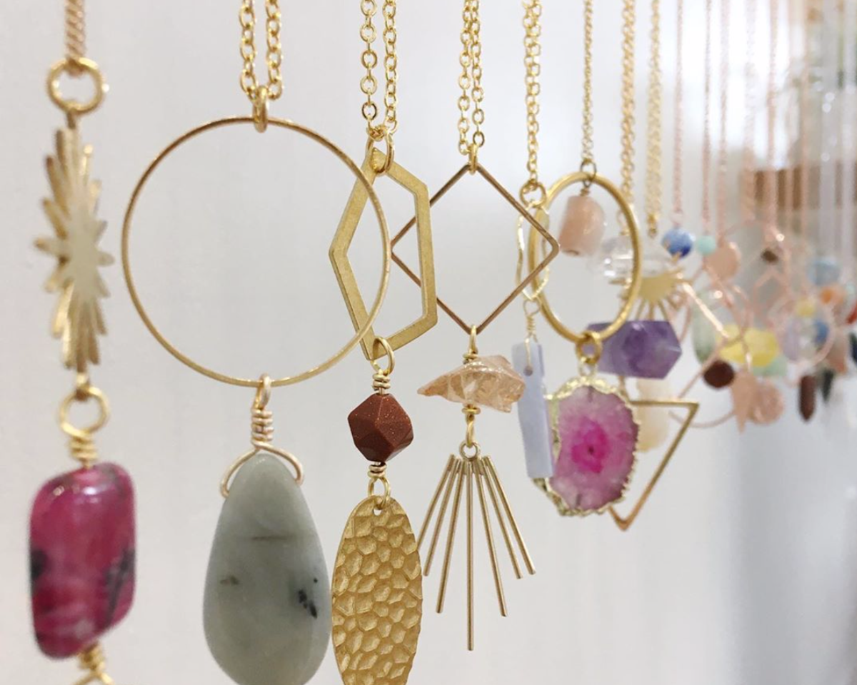 Dangling pendant necklaces featuring multicolored stones and metals