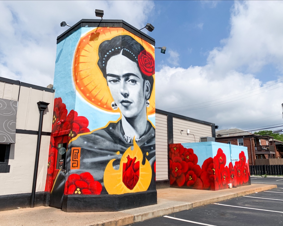 Larger-than-life mural of Frida Kahlo on the side of Barrio restaurant