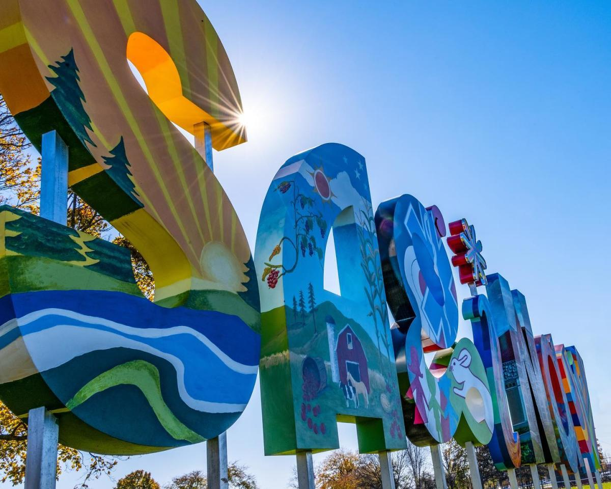 "Sun beaming through a public outdoor art installation of six-foot letters spelling ""Saginaw"", hand-painted by local artists"
