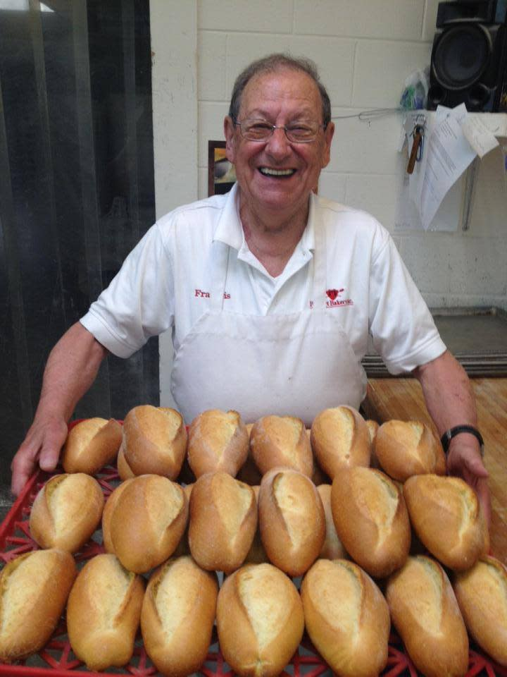 A baker holding a tray of bread At Poupart's In Lafayette, LA